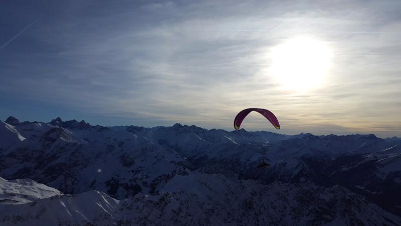 Gleitschirmflieger vor dem Panorama am Gipfel des Nebelhorn